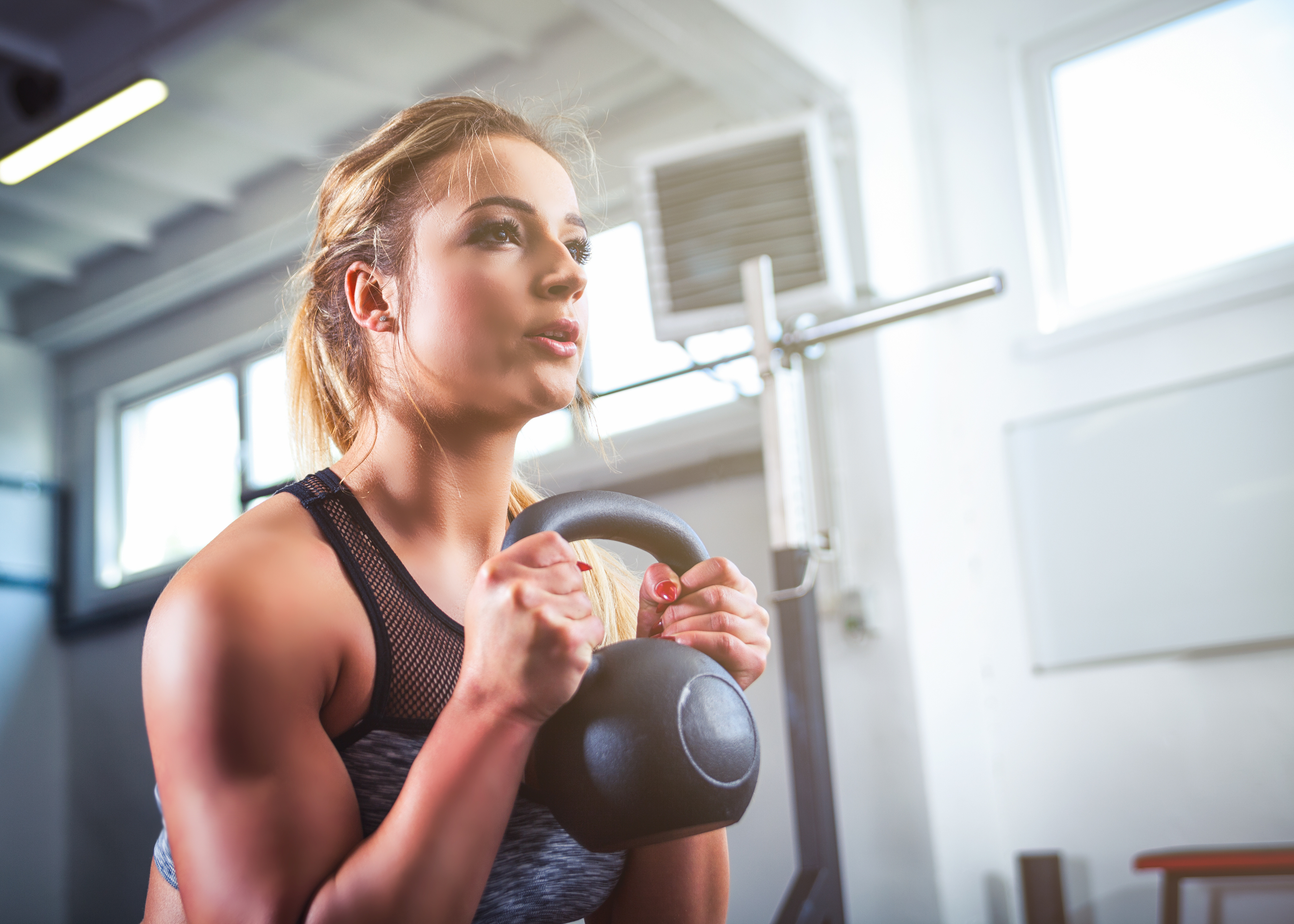 Fitness woman workout with kettlebell training at the gym